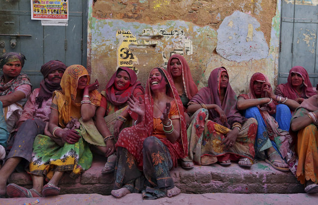 Hindu devotees laugh as they watch the religious festival of Lathmar Holi, where women beat the men with sticks, in the town of Barsana in the Uttar Pradesh region of India, March 17, 2016. (Photo by Cathal McNaughton/Reuters)