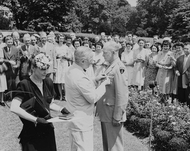 US President Harry S. Truman decorates General Dwight D. Eisenhower with the Distinguished Service Medal, as his wife Mamie Eisenhower looks on, in Washington on June 18 1945, in this handout photo provided by the United States National Archives. (Photo by Reuters/United States National Archives and Records Administration)