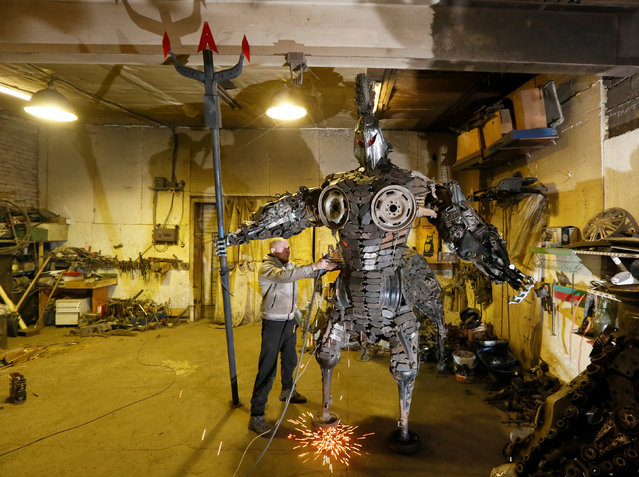 """Mechanic and welder Sergei Kulagin works on the """"Centaurus"""" sculpture, made of used car components, inside an automobile repair workshop in the Siberian town of Divnogorsk, Russia, February 9, 2017. Enthusiast Kulagin, who works as a mechanic of an automobile service station, creates sculptures made of used car parts and components during his non-working hours. (Photo by Ilya Naymushin/Reuters)"""