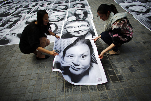 A woman, together with a friend, pastes a portrait of herself on the sidewalk as part of the Inside Out art project at Xintiandi area in downtown Shanghai, China May 14, 2014. (Photo by Carlos Barria/Reuters)