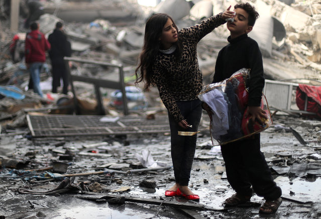 A Palestinian girl cleans the face of her brother outside their destroyed house after an Israeli missile targeted a nearby Hamas site, in Gaza City March 26, 2019. (Photo by Mohammed Salem/Reuters)