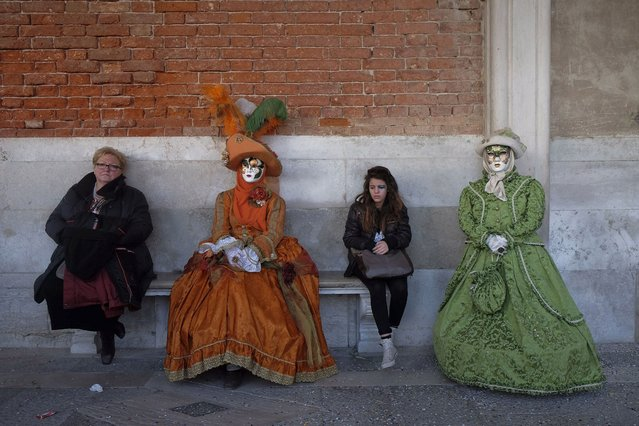 Tourists sit on a bench alongside masked revellers posing in Saint Mark's Square during the Venetian Carnival in Venice, on February 23, 2014. (Photo by Manuel Silvestri/Reuters)