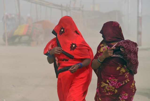 Women cover themselves during a dust storm on the banks of the river Ganges in Prayagraj, April 27, 2019. (Photo by Jitendra Prakash/Reuters)