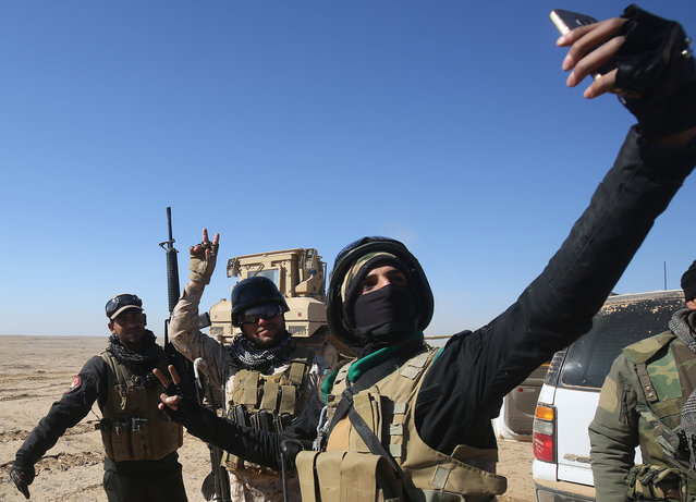 Members of the Iraqi forces, supported by the Hashed al- Shaabi (Popular Mobilisation) paramilitaries, take a selfie as they prepare to advance towards the village of Sheikh Younis, south of Mosul, after the offensive to retake the western side of the city from Islamic State (IS) group fighters commenced on February 19, 2017. (Photo by Ahmad al- Rubaye/AFP Photo)