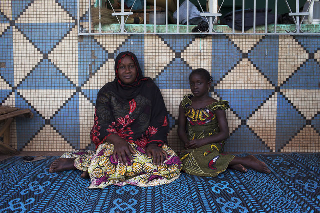 Oumou Ndiaye, 30, and her daughter Aissata Golfa, 9, pose for a picture in their house in Bamako, Mali February 20, 2014. Oumou, who is a housewife, did not go to school. As a child she hoped to marry a local businessman. She hopes her daughter will marry someone from their ethnic group when she grows up, and that she will stay in education until she is 20 years old. Aissata says that she will finish school when she is 18, and hopes to be a schoolteacher when she grows up. (Photo by Joe Penney/Reuters)