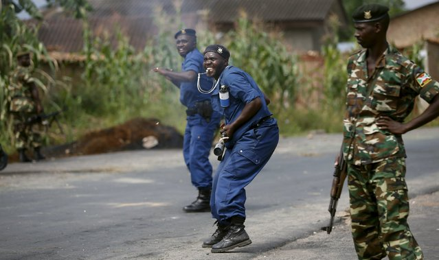 Policemen react to incoming stones thrown by protesters during a protest against Burundi President Pierre Nkurunziza and his bid for a third term in Bujumbura, Burundi, May 21, 2015. (Photo by Goran Tomasevic/Reuters)
