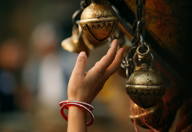 A hand of a devotee is pictured as she rings a bell while offering prayers to the chariot of God Bhairab during the Bisket festival in Bhaktapur, Nepal, April 13, 2016. (Photo by Navesh Chitrakar/Reuters)