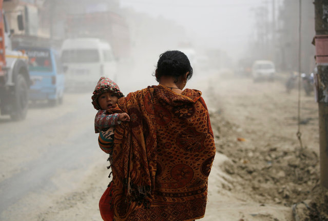 A woman carrying her child walks along the dusty road in Kathmandu, Nepal February 27, 2017. (Photo by Navesh Chitrakar/Reuters)