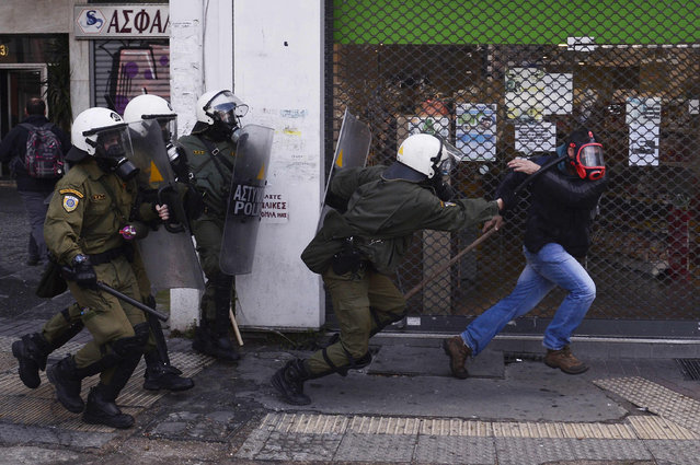 RIot police attempt to detain a man during a protest by Greek farmers against higher taxes outside the Agriculture ministry in Athens, on March 8, 2017. (Photo by Louisa Gouliamaki/AFP Photo)