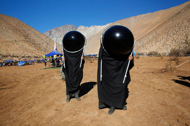 Chileans watch the sky with special suits prior to a total solar eclipse on July 2, 2019 in Paiguano, Chile. Around 25,0000 tourists arrived to Paiguano, a small town of around 1,000 inhabitants in the Elqui Valley, 650 km away Santiago. This is the only Earth's total solar eclipse of 2019 and the first one since 2017. From this point, the sun will fully disappear for around two minutes. It is best visible from a stripe in the South Pacific, Chile and Argentina. (Photo by Marcelo Hernandez/Getty Images)