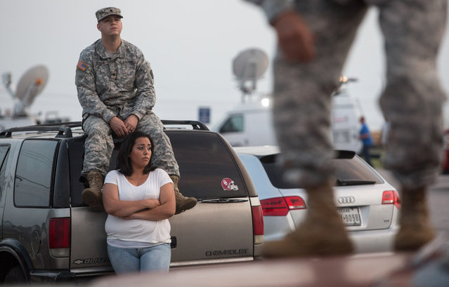 Lucy Hamlin and her husband, Spc. Timothy Hamlin, wait for permission to re-enter the Fort Hood military base, where they live, following a shooting on base on Wednesday, April 2, 2014, in Fort Hood, Texas. One person was killed and 14 injured in the shooting, and officials at the base said the shooter is believed to be dead. (Photo by Tamir Kalifa/AP Photo)