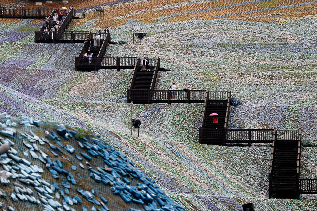 "People walk around ""The Starry Paradise"", a recreation of Van Gogh's painting ""The Starry Night"" made from discarded plastic bottles at the Embrace Cultural and Creative Park in Keelung, Northern Taiwan, 21 April 2016. (Photo by Ritchie B. Tongo/EPA)"