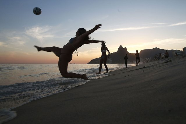 """Brazilians play altinha, a spin-off of soccer played on the beach, on Ipanema Beach on March 19, 2014 in Rio de Janeiro, Brazil. Altinha is Portuguese for """"a little higher"""" and involves players attempting to keep the ball in the air without using their hands. Brazilians play many spin-offs of soccer including altinha, footvolley and futsal. Brazil is gearing up to host the 2014 FIFA World Cup in June. (Photo by Mario Tama/Getty Images)"""