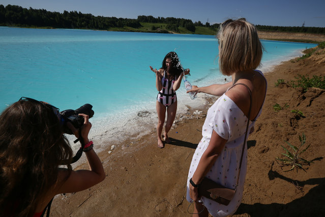 """A young woman poses for pictures by a Novosibirsk energy plant's ash dump site – nicknamed the local """"Maldives"""" – on July 11, 2019. An industrial dump site in Siberia whose turquoise lake resembles a tropical paradise has become a magnet for Instagrammers who risk their health in the toxic water to wow online followers. (Photo by Rostislav Netisov/AFP Photo)"""