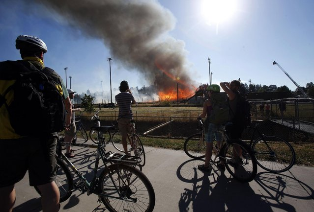 Onlooker watch the Civic Stadium fire in Eugene, Ore., Monday, June 29, 2015. (Photo by Andy Nelson/The Register-Guard via AP Photo)