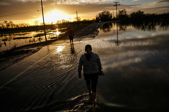 Melissa Martinez and her son, Fernando Martinez wade away from the flooded area of Gridley Road, near the Feather River as it continues to swell from the water being let out of the Oroville Dam Spillway in Gridley, Calif., on February 16, 2017. Mother and son walked into the flooded to help a friend check on their trailer home on a farm. (Phot by Marcus Yam/Los Angeles Times via Getty Images)