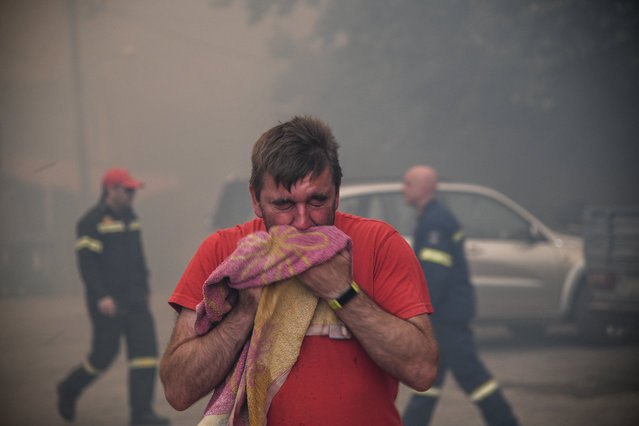 A man reacts to smoke as a wildfire burns at the village of Kontodespoti, on the island of Evia, Greece, August 13, 2019. (Photo by Michalis Karagiannis/Eurokinissi via Reuters)