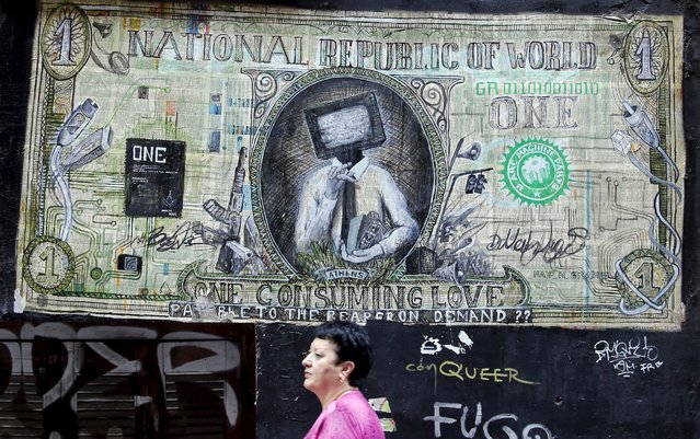 """A woman walks past a graffiti illustrating a modified dollar banknote in Athens, Greece, July 4, 2015. If a """"No"""" in Sunday's referendum eventually takes Greece out of Europe's single currency, any """"new drachma"""" or temporary payment unit could be worth as little as a fifth of the euro now in circulation. (Photo by Jean-Paul Pelissier/Reuters)"""