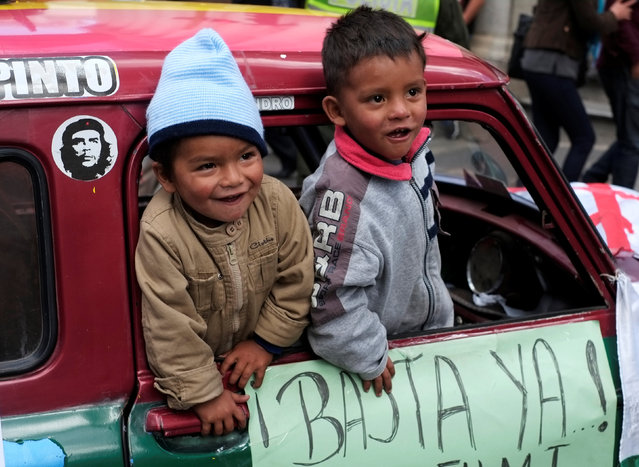 "Children are seen during a rally protest of people with physical disabilities calling on the government to provide a monthly subsidy rather than an annual one, in La Paz, Bolivia, May 5, 2016. Banner reads ""That's enough"". (Photo by David Mercado/Reuters)"