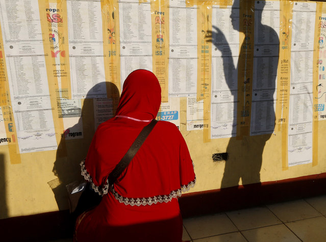 Filipino-Muslims check their names prior to voting Monday, May 13, 2019 in Metropolitan Manila in the midterm elections highlighted by a showdown between President Rodrigo Duterte's allies who aim to dominate the Senate and an opposition fighting for check and balance under a leader they regard as a looming dictator. Nearly 62 million Filipinos have registered to choose among 43,500 candidates vying for about 18,000 congressional and local posts in Monday's elections in one of Asia's most rambunctious democracies. (Photo by Bullit Marquez/AP Photo)