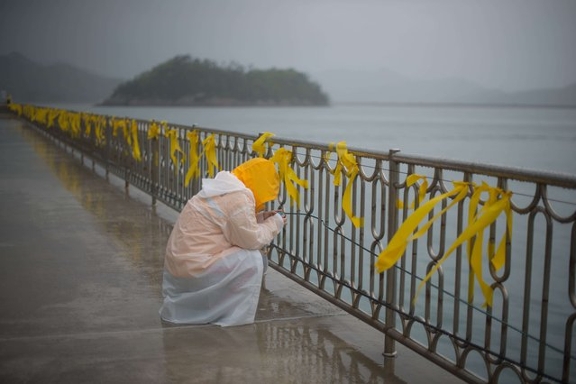 "A relative weeps before yellow ribbons at Jindo harbour where relatives of family members of the ""Sewol"" ferry are waiting for developments in the search and recovery operations, on April 27, 2014. Divers were battling atrocious weather conditions and powerful swell in their grim search for bodies believed trapped in the sunken South Korean ferry, a coastguard spokesman said. (Photo by Ed Jones/AFP Photo)"