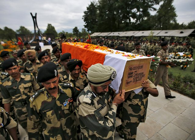 Indian Border Security Force (BSF) soldiers carry a coffin containing the body of their colleague during a wreath laying ceremony in Humhama on the outskirts of Srinagar, July 10, 2015. A Pakistani sniper shot dead an Indian border guard in the disputed region of Kashmir on Thursday, Indian authorities said, a day before the two countries' prime ministers were due to hold their first meeting in more than seven months. (Photo by Danish Ismail/Reuters)