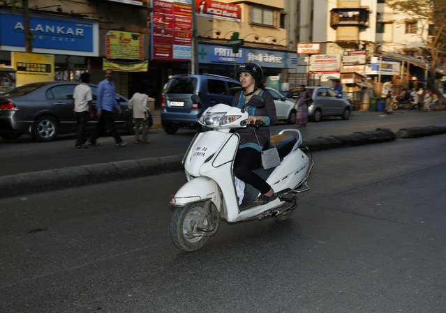 A woman rides a scooter on a Mumbai street February 5, 2014. (Photo by Mansi Thapliyal/Reuters)