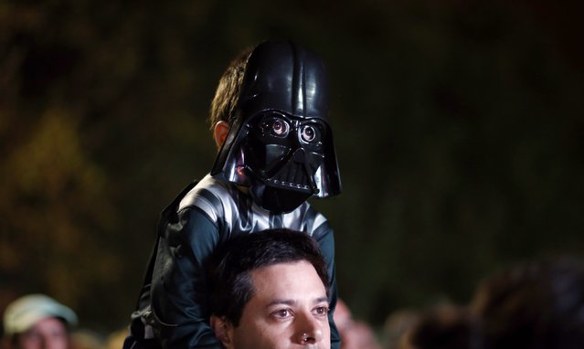 A boy wears a Darth Vader mask as he sits on a man's shoulders before the Star Wars Run race ahead of Star Wars Day in Buenos Aires May 3, 2014. (Photo by Marcos Brindicci/Reuters)