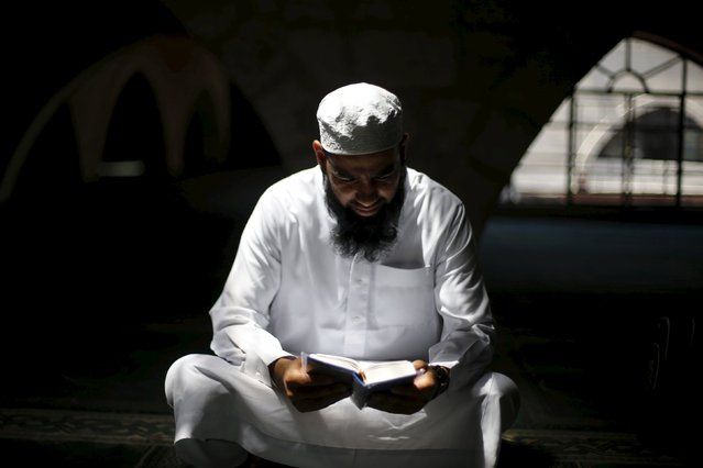 A man reads the Koran at al-Husainy mosque during the last Friday prayer of the Muslim holy month of Ramadan in downtown Amman, Jordan, July 10, 2015. (Photo by Muhammad Hamed/Reuters)