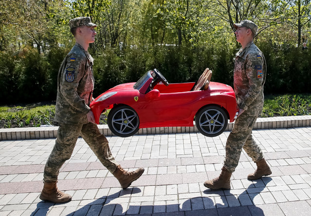Military cadets carry a toy car in a park in central Kiev, Ukraine, April 21, 2017. (Photo by Gleb Garanich/Reuters)