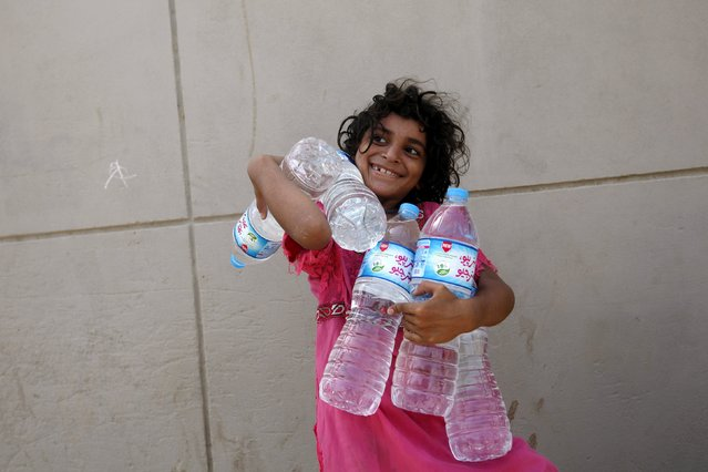 A girl smiles while holding water bottles she collected from a charity distribution point during a heatwave, outside the emergency department of Jinnah Postgraduate Medical Centre (JPMC) in Karachi, Pakistan, June 28, 2015. Sea breezes brought lower temperatures on Friday to ease a heat wave that killed more than 1,150 people around Pakistan's teeming port city of Karachi during the Muslim fasting month of Ramadan. (Photo by Akhtar Soomro/Reuters)