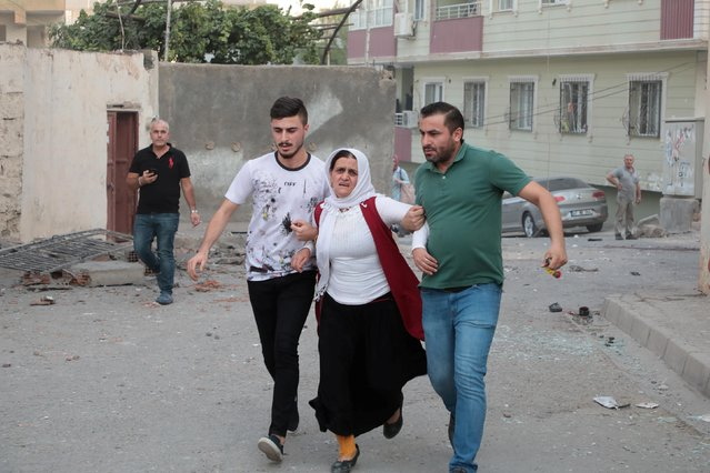 A woman is comforted by her neighboors after a rocket fired from Syria landed in their street in Nusaybin, Turkey, October 11, 2019. (Photo by Sertac Kayar/Reuters)