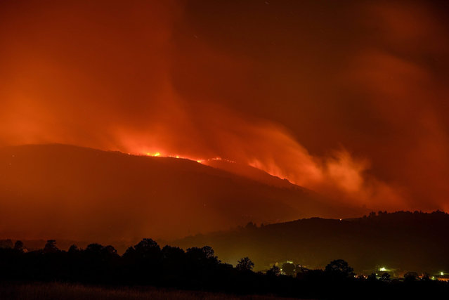 General view of a forest fire near Calvos de Randin, Galicia, northwestern Spain, 15 July 2015. Ten forest brigades, five pumps, three helicopters and six airplanes are working to extinguish the fire. (Photo by Brais Lorenzo/EPA)