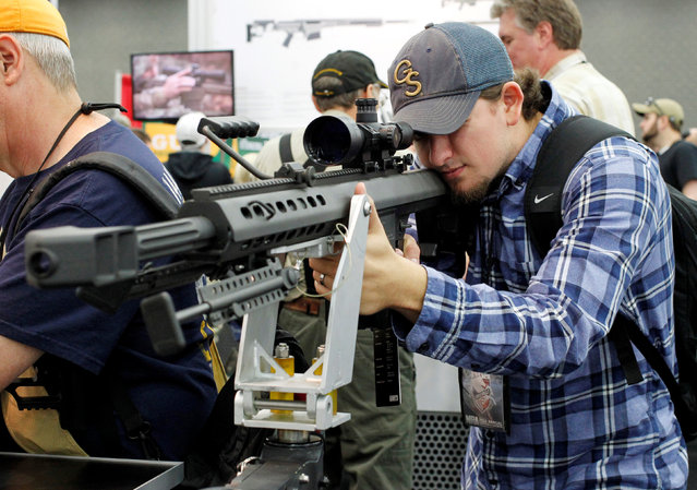 Brannan Ganas looks over guns at the Barrett Firearms booth at the National Rifle Association's annual meetings and exhibits show in Louisville, Kentucky, May 21, 2016. (Photo by John Sommers II/Reuters)