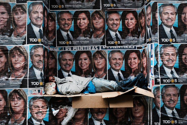 A homeless man sleeps under posters of newly elected president Alberto Fernandez and his running mate Cristina Fernández de Kirchner as people walk through a central business district  the morning after populist was declared the winner in the presidential elections on October 28, 2019 in Buenos Aires, Argentina. The Populist-leaning Fernandez beat out business-friendly incumbent Mauricio Macri in the election that could will have huge consequences for the South American country. With a sharp drop in the peso, high unemployment and rising inflation, Argentines are looking for a leader to steer the economy towards stabilization. (Photo by Spencer Platt/Getty Images)