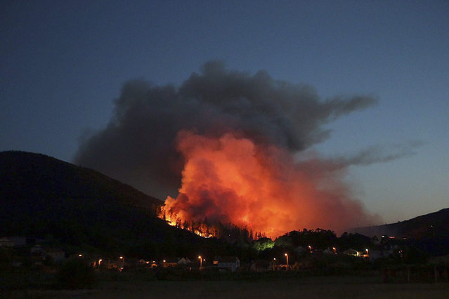 A photograph made available on 23 July 2015 a general view of a fire that broke out in the village of Padron, Galicia, northwestern Spain, late 22 July 2015. The fire was brought under control in the early hours of 23 July 2015. Early reports state that some 40 hectares of forest were affected by the fire. (Photo by EPA/Sxenick)