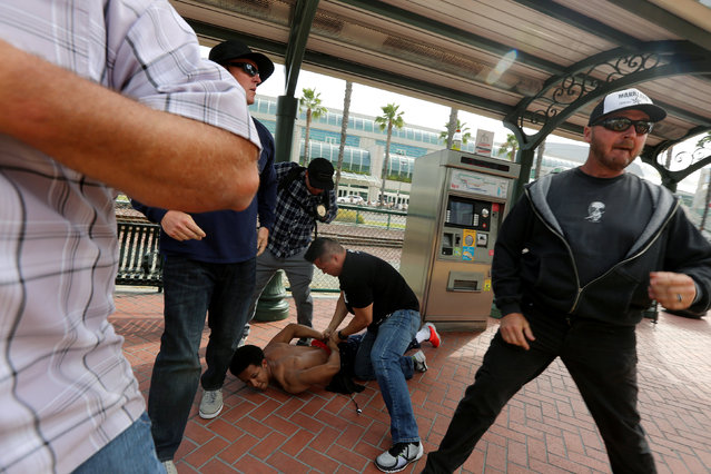 Police detain a man who was being chased by Trump supporters as supporters and anti-Trump demonstrators clash outside a campaign event for Republican U.S. presidential candidate Donald Trump in San Diego, California, U.S. May 27, 2016. (Photo by David McNew/Reuters)