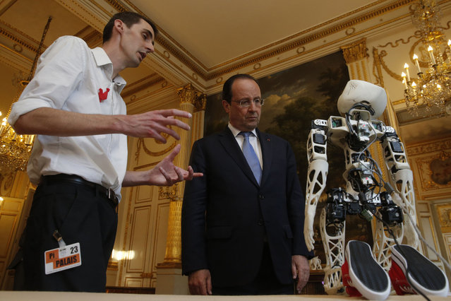 France's President Francois Hollande (C) looks at a robot after a meeting with French high tech investors at the Elysee Palace in Paris June 11, 2014. (Photo by Christian Hartmann/Reuters)