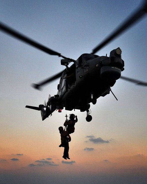 Winch Transfers training being carried out on the flight deck of HMS Montrose by L(Phot) Alex Knott taken from his portfolio which earned him the title of Royal Navy Photographer of the Year 2014. (Photo by Alex Knott/PA Wire)