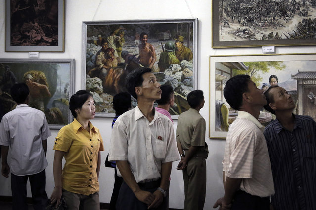 North Koreans look at paintings on display, Sunday, July 26, 2015, in Pyongyang, North Korea. The art exhibition comprised of works by different local artists on the life of North Koreans during the Japanese occupation and before their country's liberation from the Korean War. North Korea celebrates its 62nd year anniversary of the armistice that ended the Korean War on July 27. (Photo by Wong Maye-E/AP Photo)