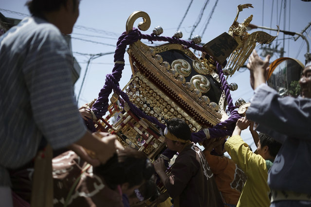 "Participants clad in traditional ""happi"" coats swing the ""mikoshi"", or portable shrine to left and right in Tenno-sai festival at Susanoo Shrine Saturday, June 3, 2017, in Tokyo. Tenno-sai festival is an annual traditional festival which is believed to expel a contagious disease in summer to protect people. (Photo by Eugene Hoshiko/AP Photo)"