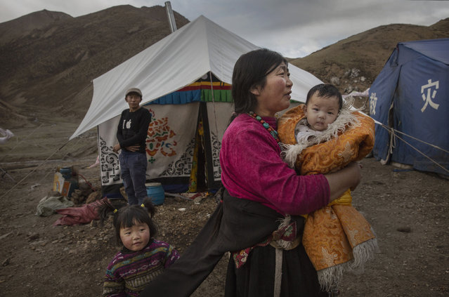 A Tibetan woman holds a baby as she stands outside a tent at a temporary camp for cordycep pickers on May 23, 2016 on the Tibetan Plateau near Zadoi in the Yushu Tibetan Autonomous Prefecture of Qinghai province. (Photo by Kevin Frayer/Getty Images)