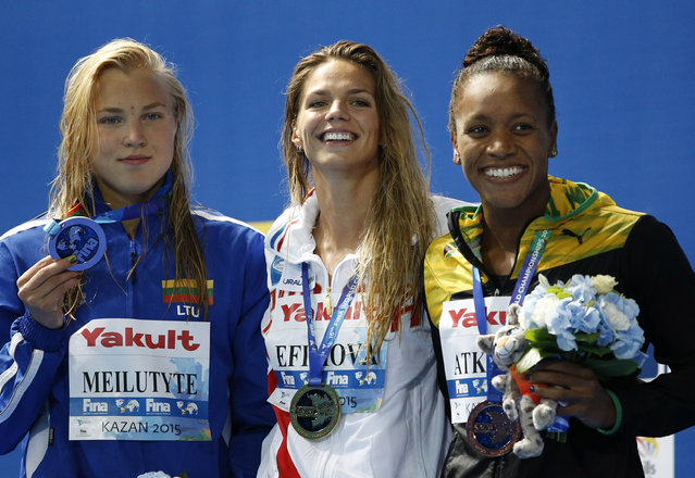 Russia's gold medal winner Yuliya Efimova is flanked by Lithuania's silver medal winner Ruta Meilutyte and Jamaica's bronze medal winner sAlia Atkinson during the ceremony for the the women's 100m breaststroke final at the Swimming World Championships in Kazan, Russia, Tuesday, August 4, 2015. (Photo by Sergei Grits/AP Photo)