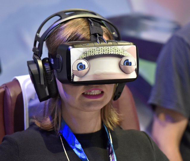 A woman wears a virtual reality  head-mounted display  at the gamescom fair in Cologne, Germany, Wednesday, August 5, 2015. (Photo by Martin Meissner/AP Photo)