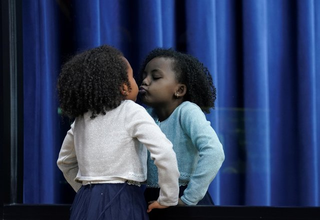 Elgrace Bereket, 4, kisses her reflection on mirrored glass while onstage with U.S. President Donald Trump, who was addressing a summit on child care and paid leave at the White House in Washington, U.S., December 12, 2019. (Photo by Kevin Lamarque/Reuters)