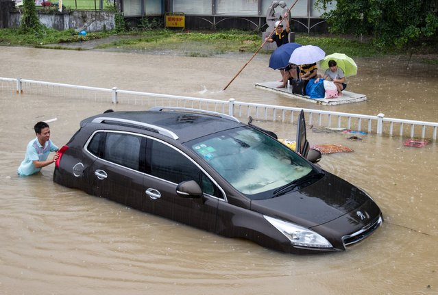 A trapped car is pushed along a flooded street after typhoon Soudelor hit Fuzhou, Fujian province, China, August 9, 2015. The typhoon battered China's east coast on Sunday, killing eight people and forcing authorities to cancel hundreds of flights and evacuate more than 163,000 people. (Photo by Reuters/Stringer)