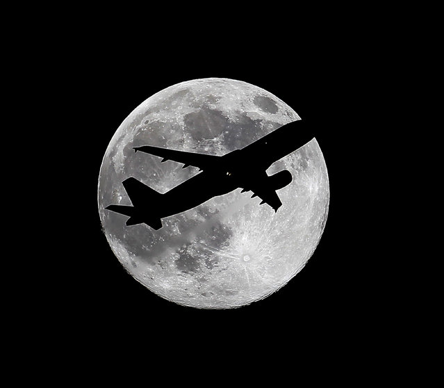 """One day before a """"supermoon"""", Virgin America flight VX415 from New York (JFK) to Los Angeles (LAX) crosses the waxing gibbous moon on its final approach to Los Angeles Airport as viewed from Whittier, Calif., Friday, July 11, 2014. (Photo by Nick Ut/AP Photo)"""