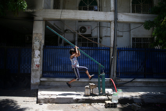 A boy pulls a lever as he fills water containers, in the rebel held besieged town of Douma, eastern Damascus suburb of Ghouta, Syria, June 23, 2016. (Photo by Bassam Khabieh/Reuters)