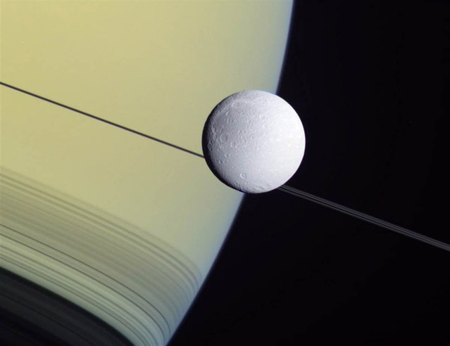 This wide-angle view from NASA's Cassini probe shows the Saturnian moon Dione set against the giant planet's disk and rings on May 2 2012