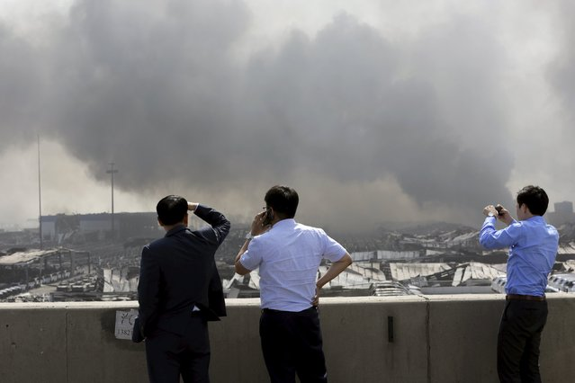 Three Korean businessmen look on from a highway near the site of the explosions at the Binhai new district, Tianjin, August 13, 2015. (Photo by Jason Lee/Reuters)